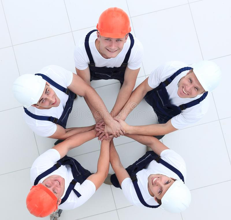 Group of construction workers with hands clasped together. Concept of the team.a close-knit group of builders royalty free stock photography