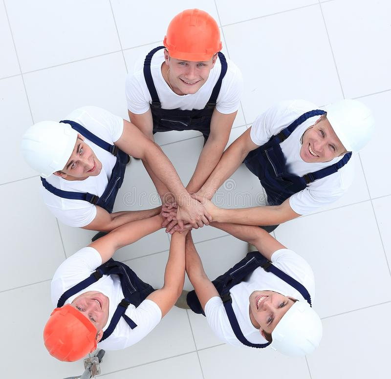 Group of construction workers with hands clasped together. Concept of the team.a close-knit group of builders royalty free stock images
