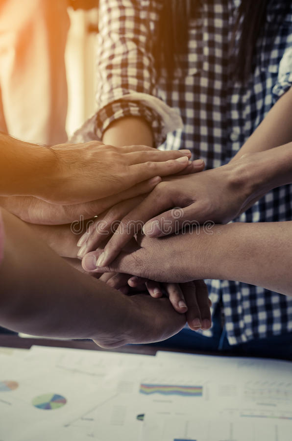 Concept of teamwork: Close-Up of hands business team showing unity with putting their hands together royalty free stock photography