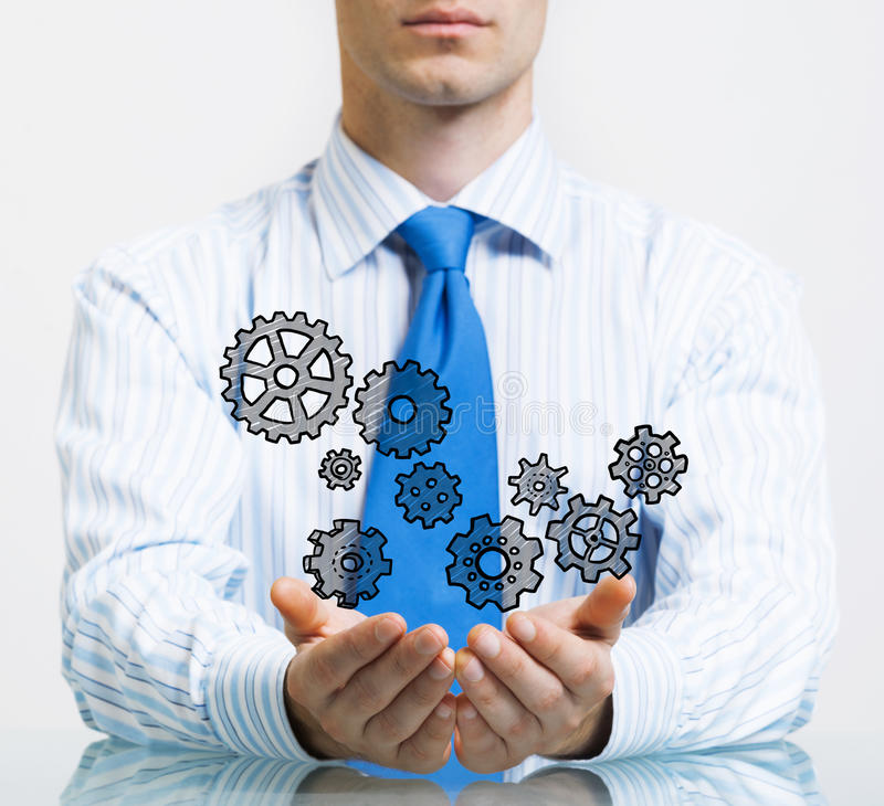 Concept of teamwork and cooperation. Close up of businessman sitting at table and showing gear mechanism in palms stock photography