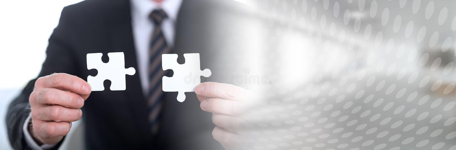 Concept of teamwork; panoramic banner. Hands joining two puzzle pieces, teamwork concept; panoramic banner royalty free stock photography