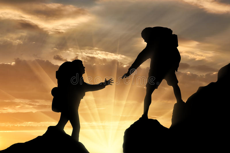 Concept of teamwork and trust. Climber reaches out to his partner by helping each other. Concept of teamwork and trust stock photo