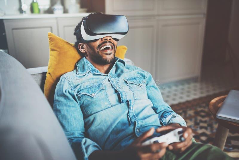 Concept technologie, gokken, vermaak en mensen Gebaarde Afrikaanse mens die van virtuele werkelijkheidsglazen genieten terwijl stock fotografie
