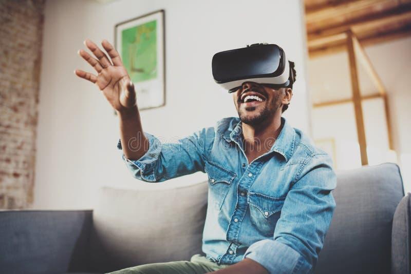 Concept technologie, gokken, vermaak en mensen Gelukkige gebaarde Afrikaanse mens die van virtuele werkelijkheidsglazen genieten  stock afbeelding