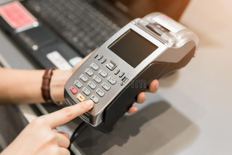 Concept of technology in buying without using cash. Close up of hand use credit card swiping machine to pay. Concept of technology in buying without using cash stock photography