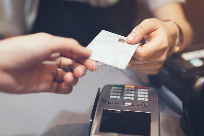 Concept of technology in buying without using cash. Close up of hand use credit card swiping machine to pay royalty free stock image