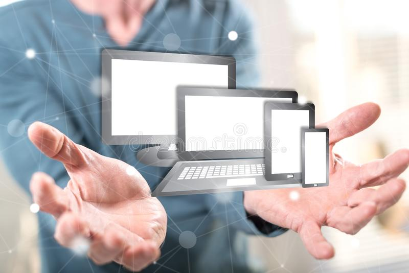 Concept of technology devices. Technology devices concept above the hands of a man in background stock photo