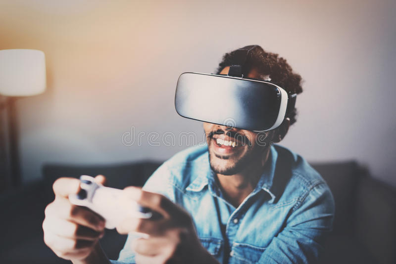 Concept of technology,gaming,entertainment and people.African man playing virtual reality glasses video game while. Relaxing in living room at home.Selective