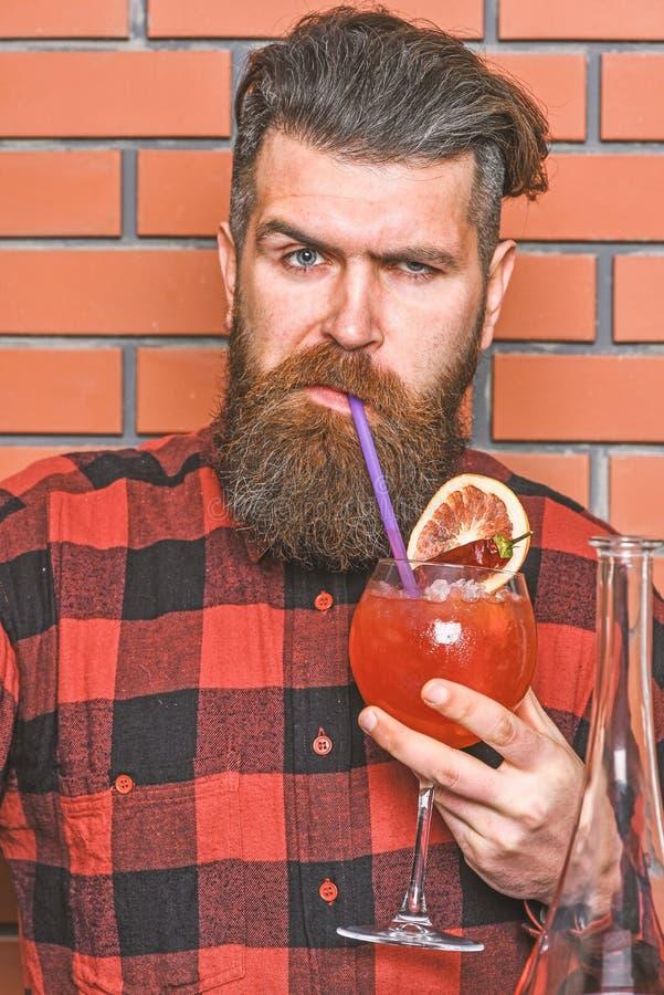 Concept tenant le bar L'homme dans la chemise à carreaux sur des goûts de fond de mur de briques boit Barman avec la longues barb photos stock
