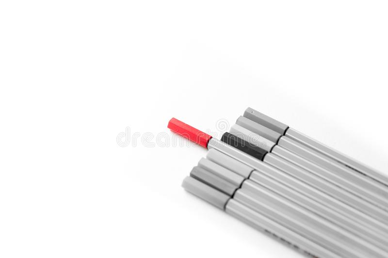 Concept of think different with one red marker standing out from the crowd, symbol and concept of distinctiveness, dissent, stock images