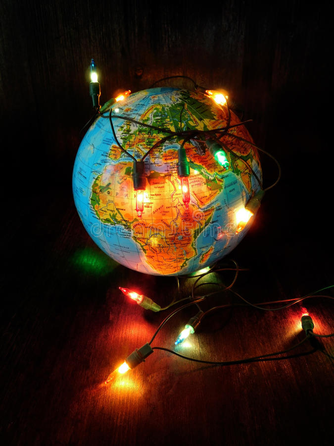 Concept of a threat of the greenhouse effect caused by incandescent lamps. Abstract depiction of the Earth tied by a chain of lamps and a threat of the global royalty free stock photo