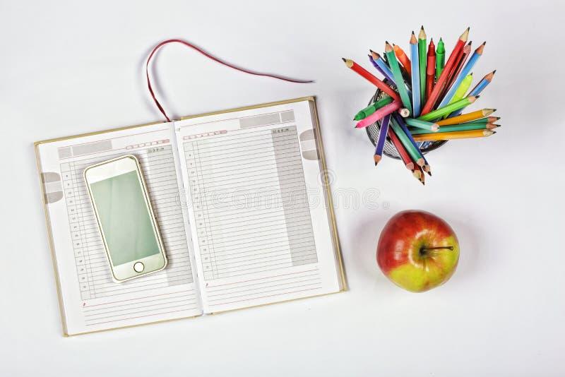 Concept tijd planning, blocnote, blanco pagina, telefoon, kleurpotloden en pennen Apple planning, schoolprogramma Nieuw idee bove stock foto's