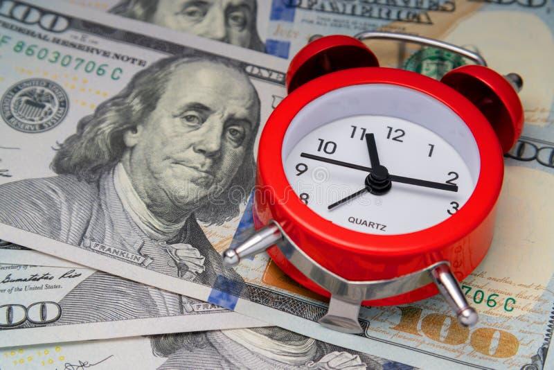 concept tijdwaarde Koele wekker op Amerikaanse dollars Cheboksary, Rusland, 11/25/2018 stock fotografie