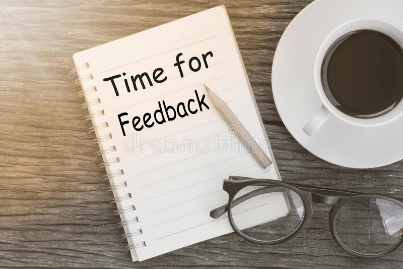 Concept Time for Feedback message on notebook with glasses, pencil and coffee cup on wooden table. royalty free stock photography