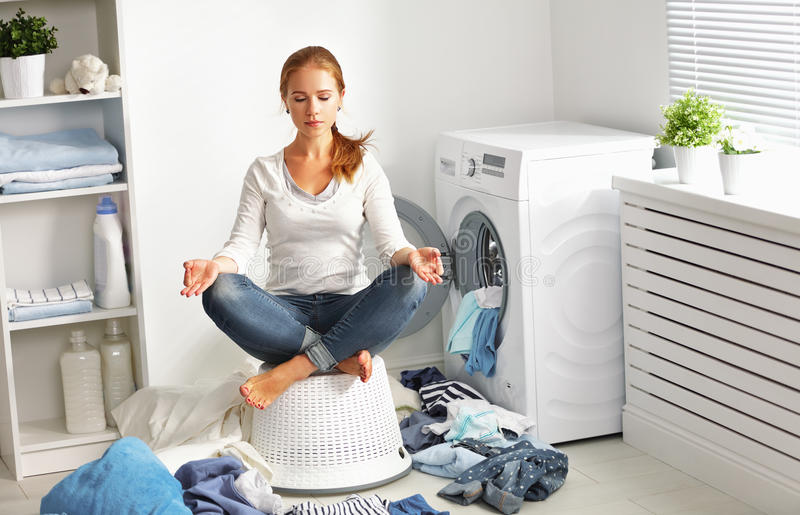 Concept. tired housewife meditates in lotus position in laundry. Room near washing machine and dirty clothes royalty free stock photos