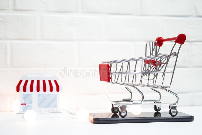 Concept on the topic of sales. Supermarket Trolley with smartphone and luminous garlands on the background of the store royalty free stock images