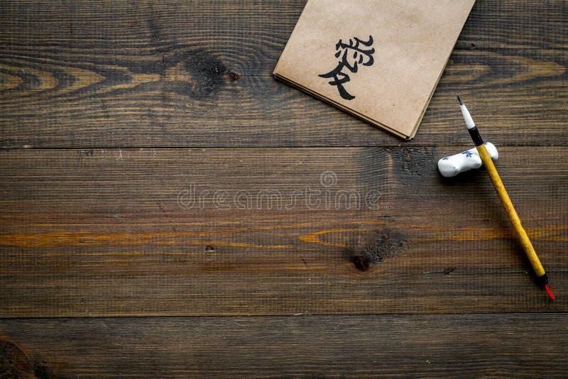Concept traditionnel chinois de calligraphie Symbole asiatique d'hiéroglyphe dans le carnet de papier de métier près du stylo de  photos libres de droits