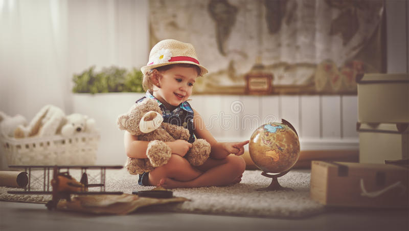 Concept travel. child girl at home dreaming of travel and tourism. Exploring the world map and globe royalty free stock photos