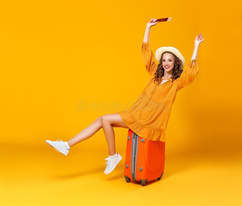 Concept of travel. happy woman girl with suitcase and  passport on  yellow background stock photo