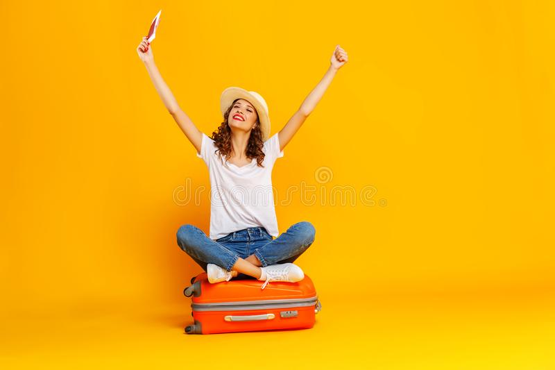 Concept of travel. happy woman girl with suitcase and  passport on  yellow background stock image