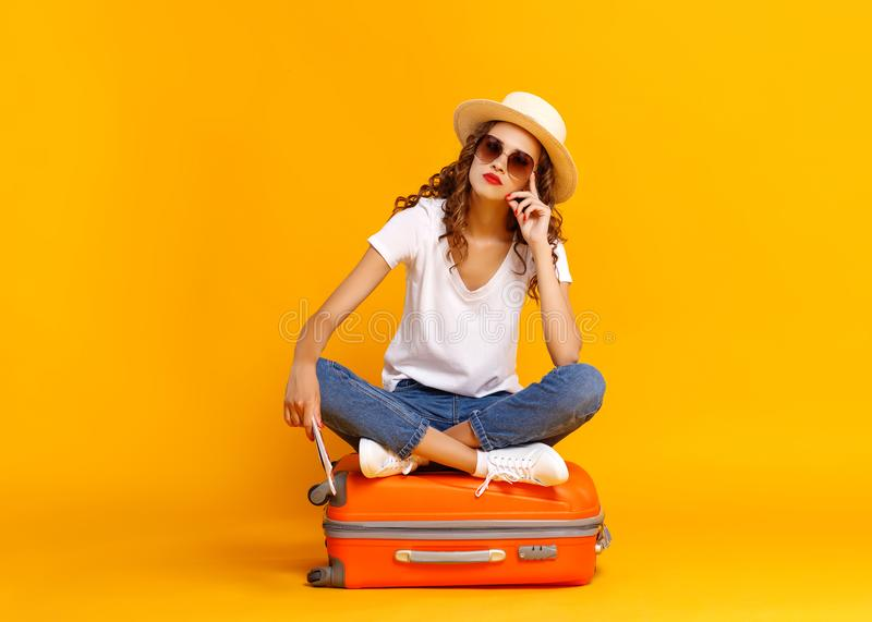 Concept of travel. happy woman girl with suitcase and  passport on  yellow background stock photography