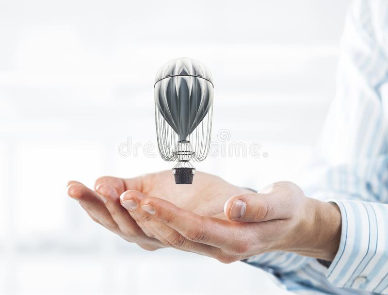 Concept of travel and imagination with aerostat in male palms. M. Close of businessman holding aerostat balloon in palms. Mixed media stock photo