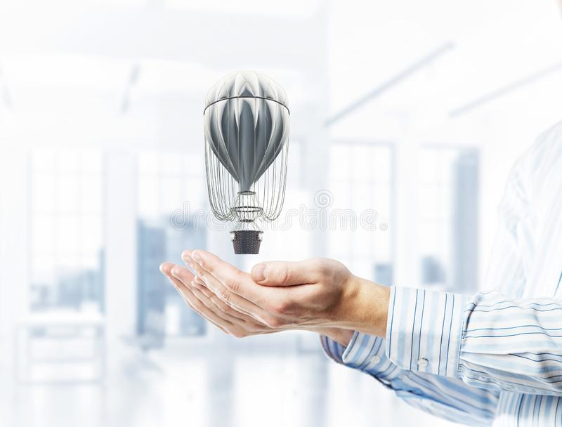 Concept of travel and imagination with aerostat in male palms. M. Close of businessman holding aerostat balloon in palms. Mixed media royalty free stock photography