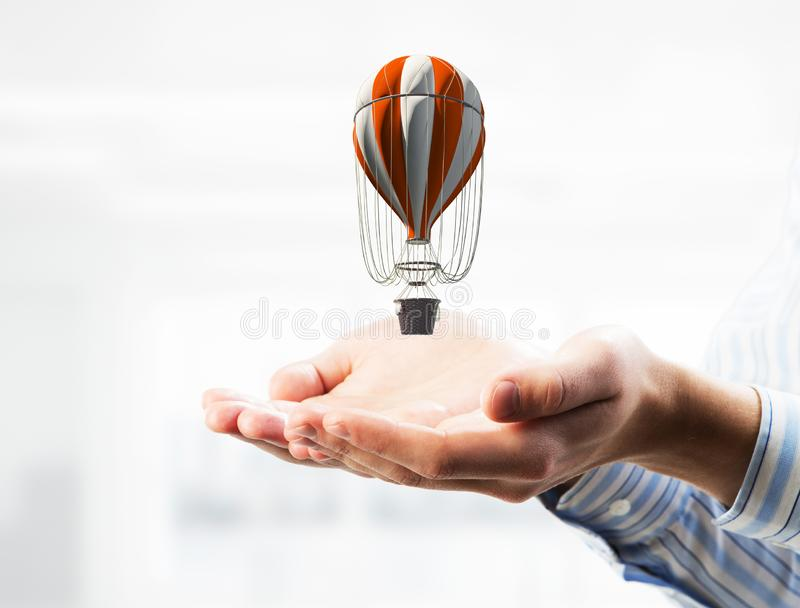 Concept of travel and imagination with aerostat in male palms. Mixed media. Close of businessman holding aerostat balloon in palms. Mixed media stock images