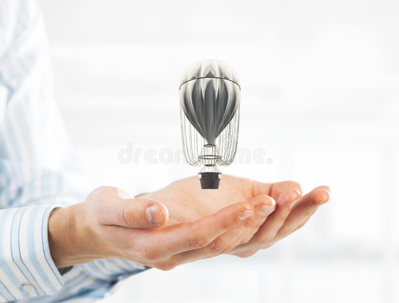 Concept of travel and imagination with aerostat in male palms. Mixed media. Close of businessman holding aerostat balloon in palms. Mixed media royalty free stock image