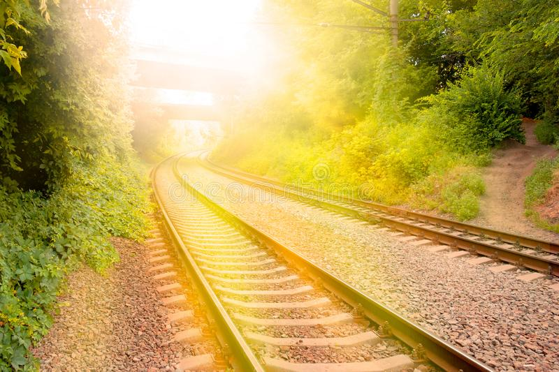 Concept of travel by train on railroads. Rails track is going into horizon with light flash. Cargo and passenger transportation stock photography
