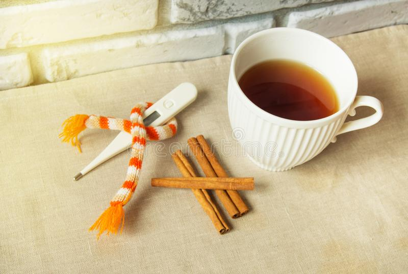 Concept of treating colds - hot tea with cinnamon, thermometer and scarf.  royalty free stock photography