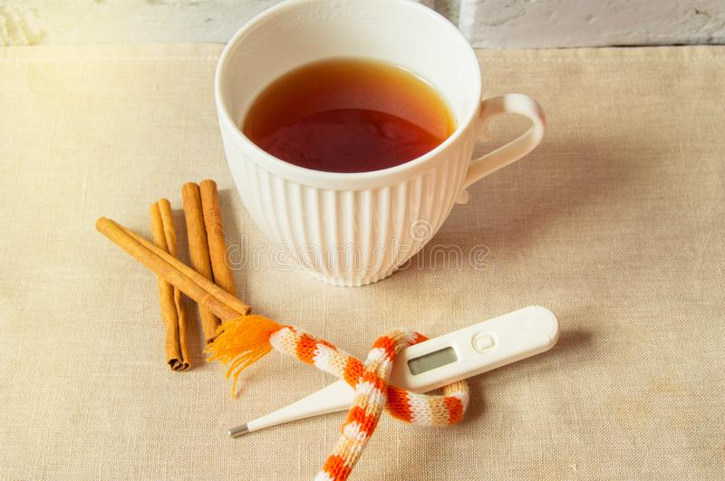 Concept of treating colds - hot tea with cinnamon, thermometer and scarf.  stock image