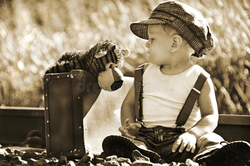 Concept two best friends travelling journey of life together. Endearing portrait in sepia tones of a little infant boy sitting beside the railroad lines with his stock image
