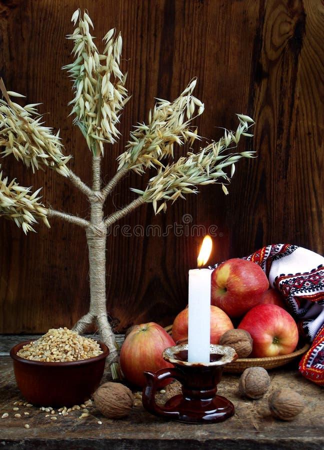 Concept ukrainien de Noël pour la carte de voeux Composition de didukh de symbole de Noël, bougie brûlante, pommes, noix, blé sur photos libres de droits