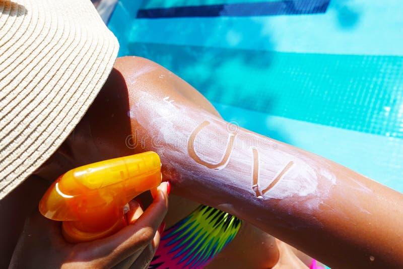 Concept ultra-violet de protection avec le texte UV sur la protection solaire sur le bras de jeune femme à la piscine image stock