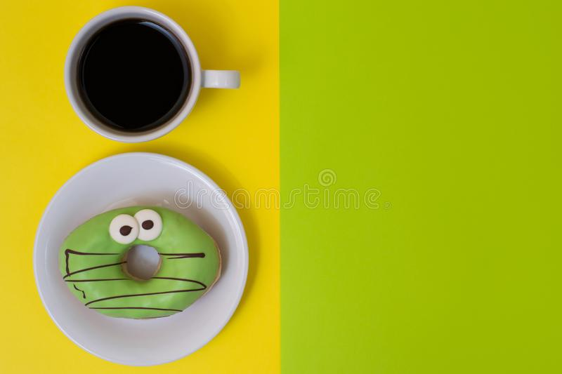 Concept of unhealthy dieting and snacks. Sugary glazed doughnut. With cup of strong black coffee isolated on yellow background. Place for text on the green royalty free stock photos