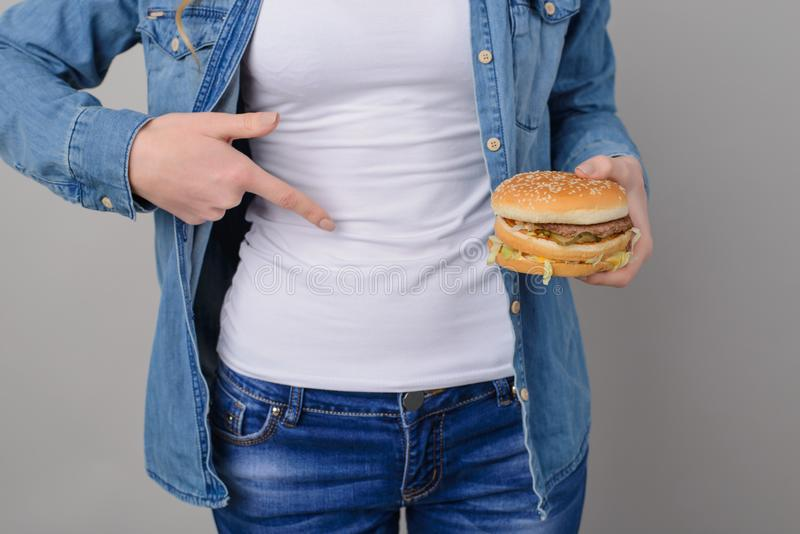 Concept of unhealthy eating and overeating. Woman has problems w royalty free stock images