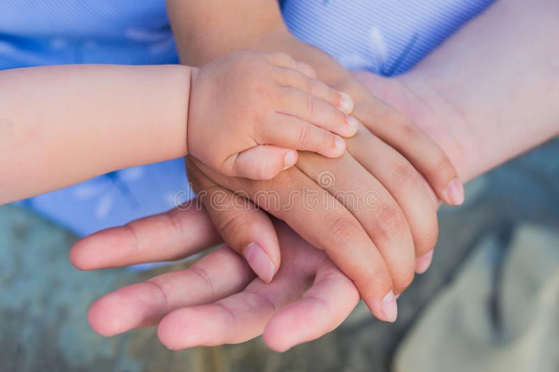 Concept of unity, support, protection, happiness. Child hand closeup into parents. Hands of father, mother, keep hand little baby stock image