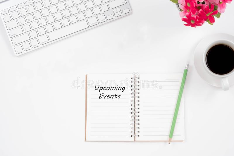 Concept Upcoming Events message on notebook, keyboard,with pencil and coffee cup. Top viwe of modern workplace. royalty free stock photos