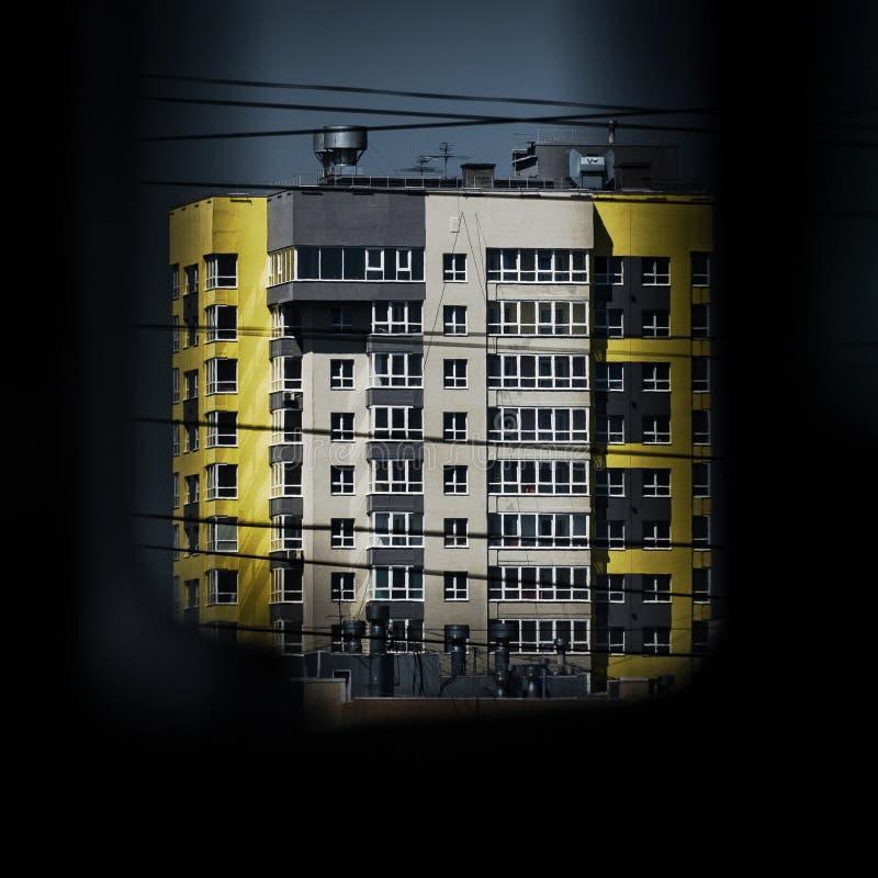 Concept urbain de vision : Immeuble moderne sur Sunny Day As Seen Through un trou images stock
