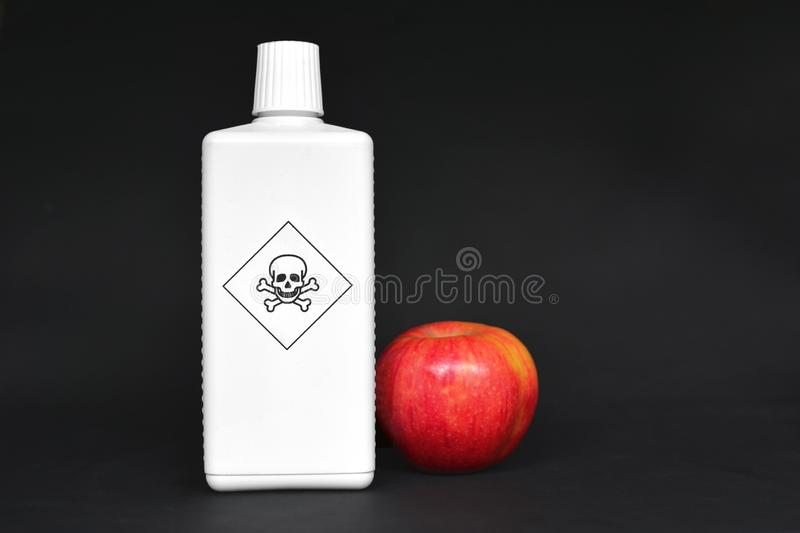 Concept for usage of dangerous pesticides in agricultural food products with red apple next to white bottle with poisonous warning stock images
