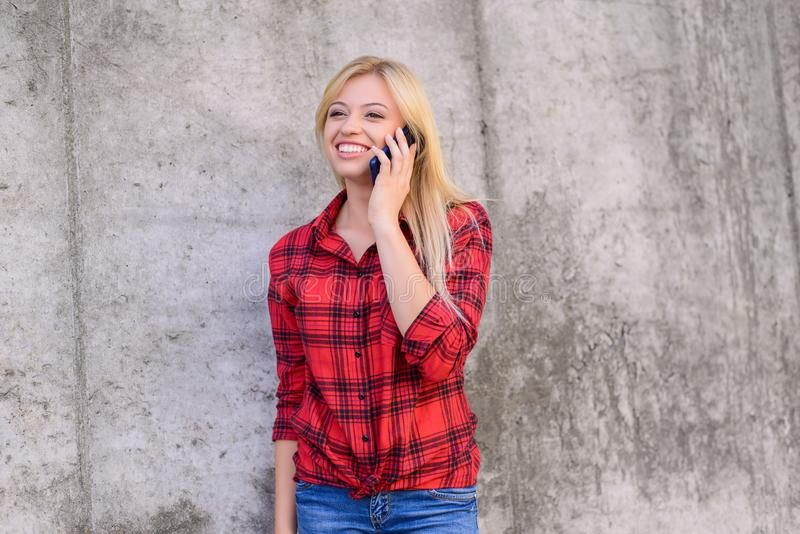 Concept of using modern technology. Smiling woman in casual clothes calling her friend. Cell cellphone smart smartphone mobile tel stock image
