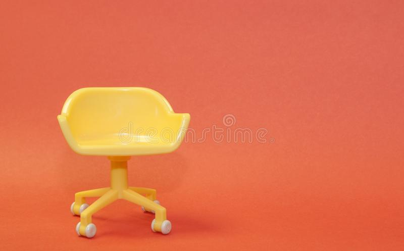 Concept of vacant chair. Yellow stool on orange clean background. Photo in minimal style. Design, interior, wall, room, business, office, pastel, empty, seat royalty free stock photos