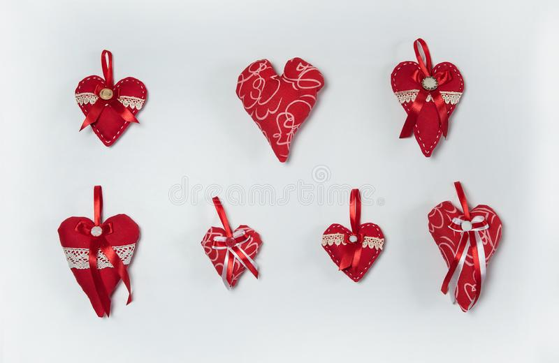A collection of hand-sewn textile hearts decorated with ribbons and lace on a white background. royalty free stock images