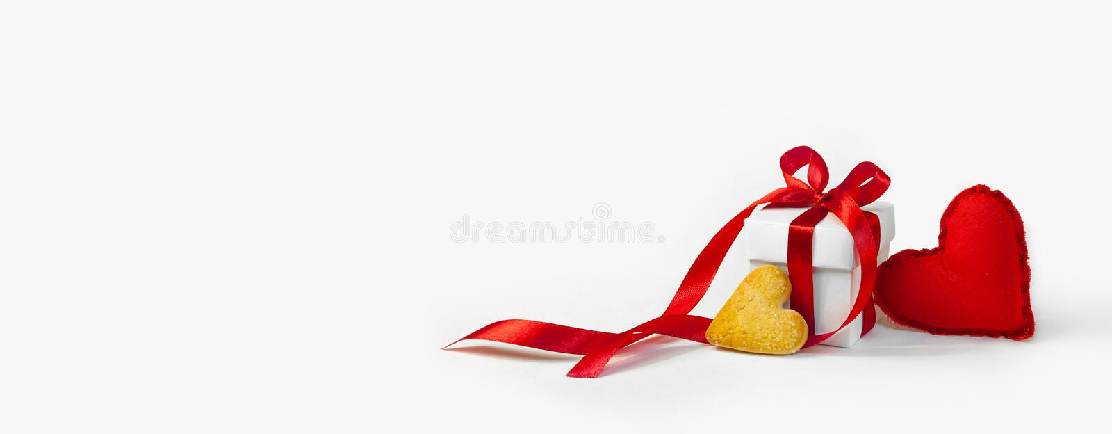 Concept Valentine`s Day. Red Soft Toy Heart and White Gift Box with Red Ribbon and Little Cookie in the Shape of Heart on Light B royalty free stock image