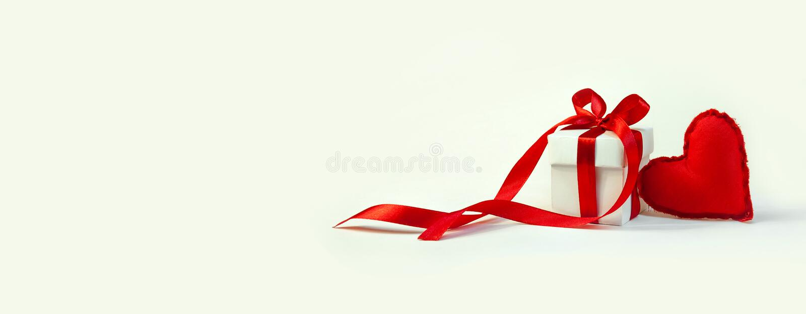 Concept Valentine`s Day. Small Soft Red Toy Heart and White Gift Box with Red Ribbon on Light Background. Banner. Copy Space of Y stock photos