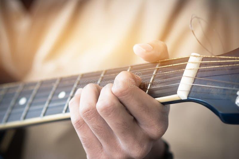 Concept van de muziek het speelgitaar: De mensen van de handen Jonge mens dat het gitaristspel voor levend in overleg toont royalty-vrije stock afbeelding