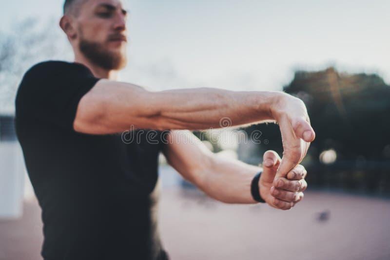 Concept van de training het openluchtlevensstijl Jonge mens die zijn wapenspieren uitrekken alvorens op te leiden Het jonge Spier royalty-vrije stock fotografie