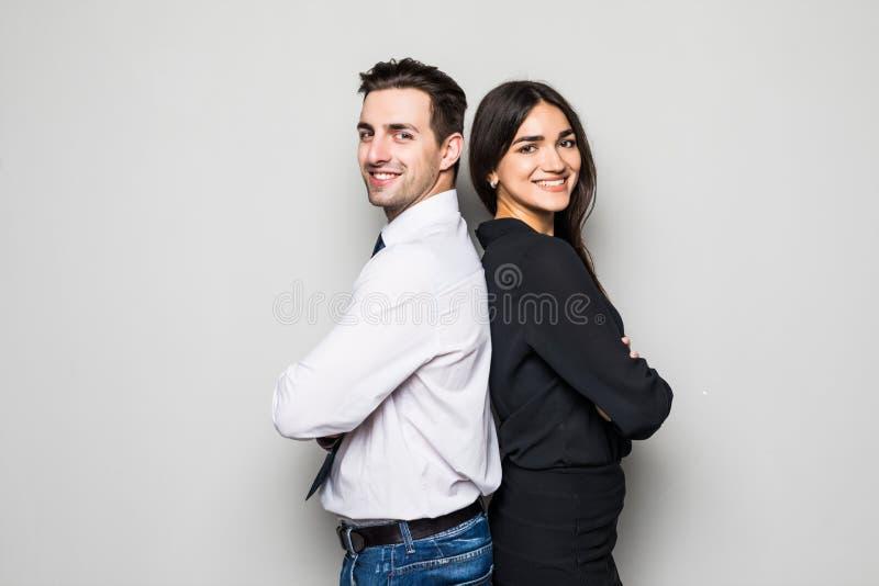 Concept vennootschap in zaken Jonge man en vrouw die zich rijtjes met gekruiste handen tegen grijze achtergrond bevinden royalty-vrije stock afbeelding
