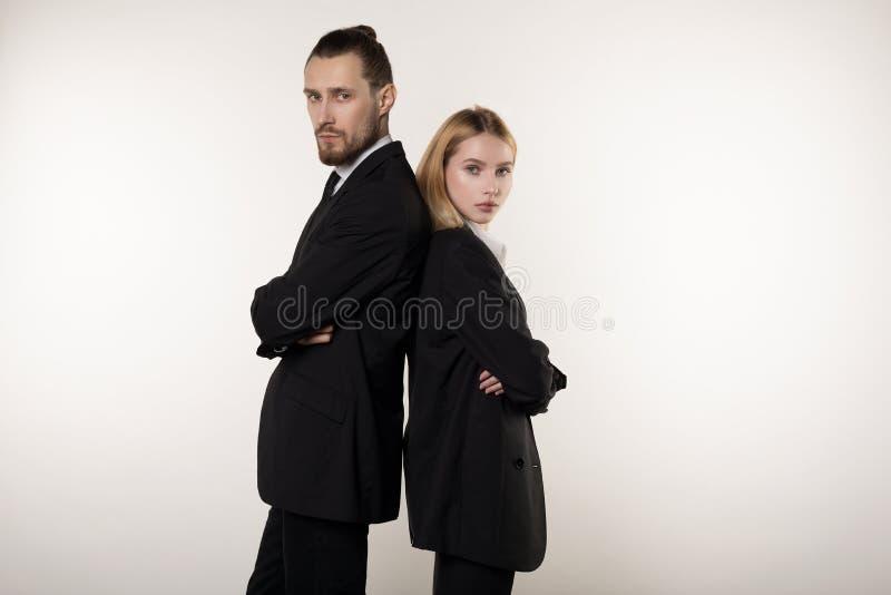 Concept vennootschap in zaken Knappe man en mooie vrouw, allebei in zwarte kostuums die zich rijtjes met bevinden stock fotografie